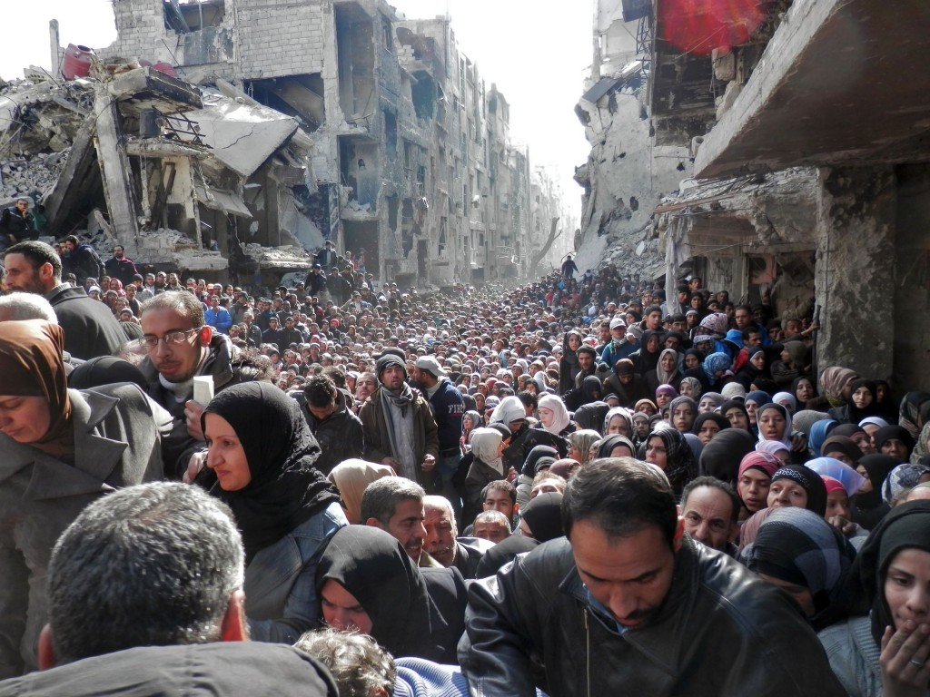 "This is the Yarmouk refugee camp, which houses Palestinians, in Damascus. It's been described as a ""living hell"" and ""the worst place on Earth,"" as a result of the utterly miserable living conditions. This 2014 photo, which shows masses of people waiting for food and aid amidst bombed-out buildings, is a perfect encapsulation of how bad things have gotten in Syria. (United Nation Relief and Works Agency/Getty Images)"