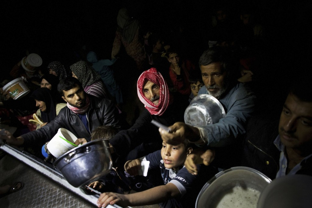 Displaced Syrians wait for food from an NGO near Azaz, Syria, in 2012. (AP Photo/Manu Brabo)